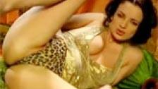 Preciosa morena con vestido dorado haciéndose un dedo