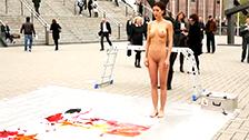 Die Künstlerin Milo Moiré malt ein Bild, indem sie Farbe aus ihrer Muschi auswirft