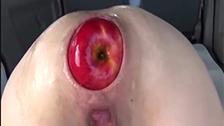 Cette femme écarte son trou du cul pour prendre des pommes dedans