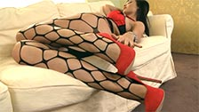 Audrey in fishnet pantyhose and seducing the camera with her feet