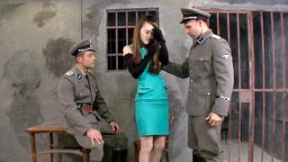 Misha Cross transa com dois oficiais nazistas em uma cela