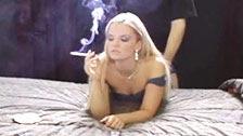 Une blonde se fait baiser passivement par derrière en fumant